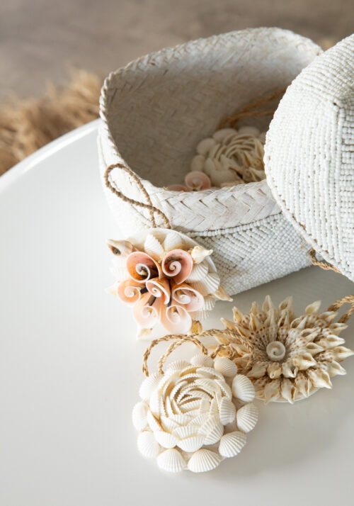 close up of white beaded basket with shell ornaments
