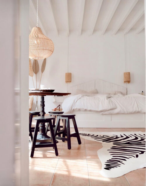 white bedroom with bed and table and hanging lamp