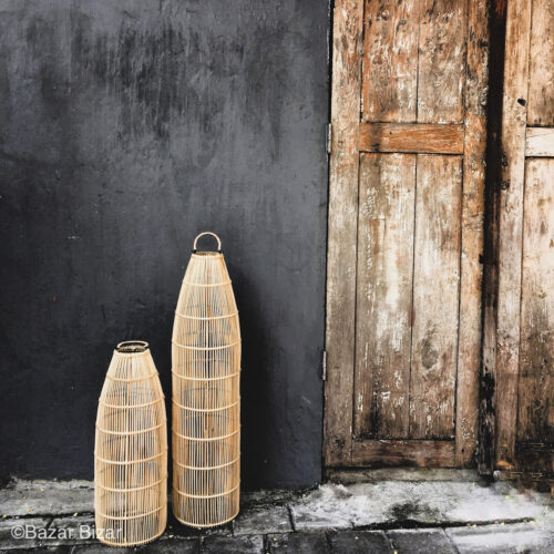 two natural standing lamps in front of black wall