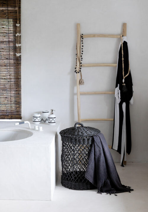 bathroom with black basket and ladder with necklages and bathrobe
