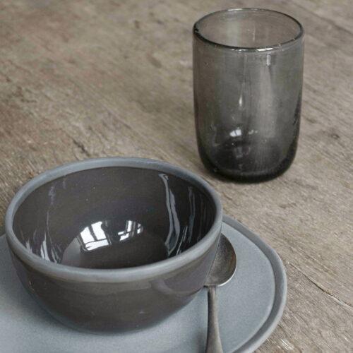 close up van kom, bord en glas in grijs