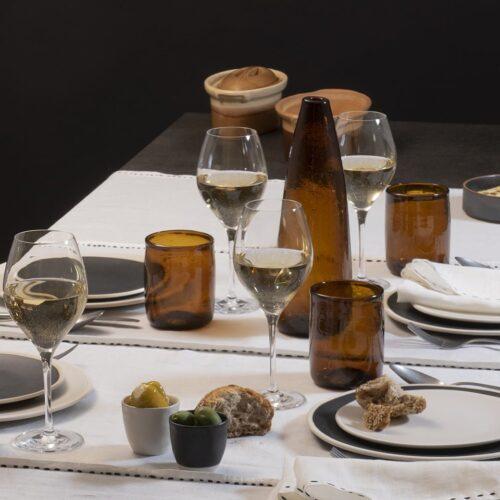 tafelsetting van waterglazen, wijnglazen en waterkan met borden