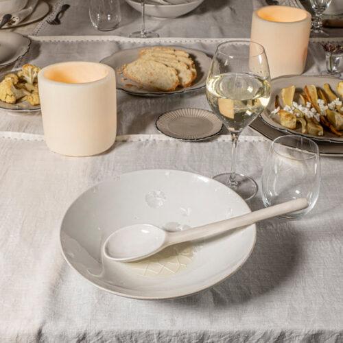 tafelsetting van wit bord met lepel en daaromheen glas wijn, kandelaar en borden met ontbijt