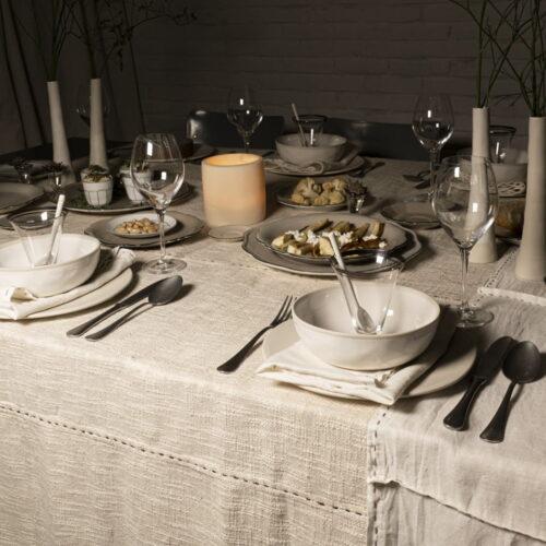 gedekte tafel met kommen, bestek, schalen voedsel, kandelaars en kaarsen