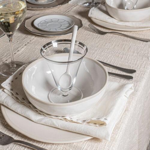 gedekte tafel in wit met close up van bord met daarop servet, schaal, glas en lepe