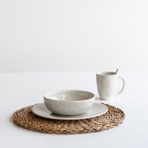 placemat met daarop bord, kom en koffiemok in wit op witte achtergrond