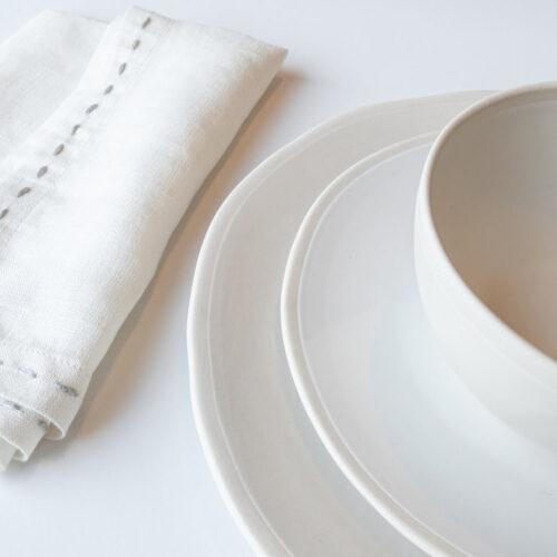 close up van gestapelde witte borden met daarop een kom en wit server
