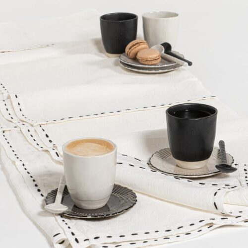 table setting with black and white coffee mugs on a linen tablecloth