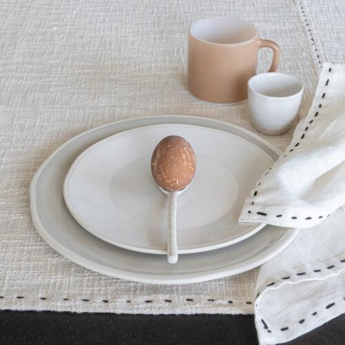 ei op witte lepel op wit bord op wit tafelkleed
