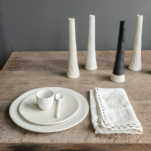 houten tafel met daarop vaasjes, witte borden en espressomok