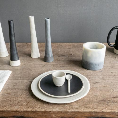 vaasjes, borden met espressomok en kaars op houten tafel