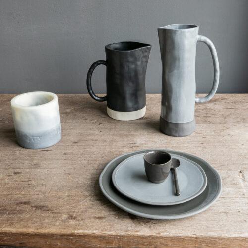 tafelsetting van borden, kannen en kaars in grijs tinten op houten tafel