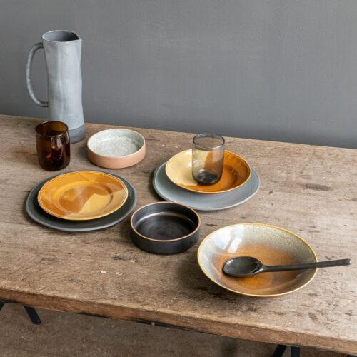 tafelsetting in aardse tonen schalen en borden op houten tafel