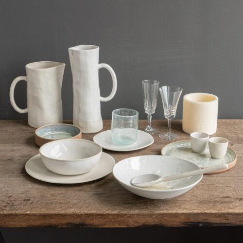 tafelsetting met witte kannen, schalen en glazen op houten tafel