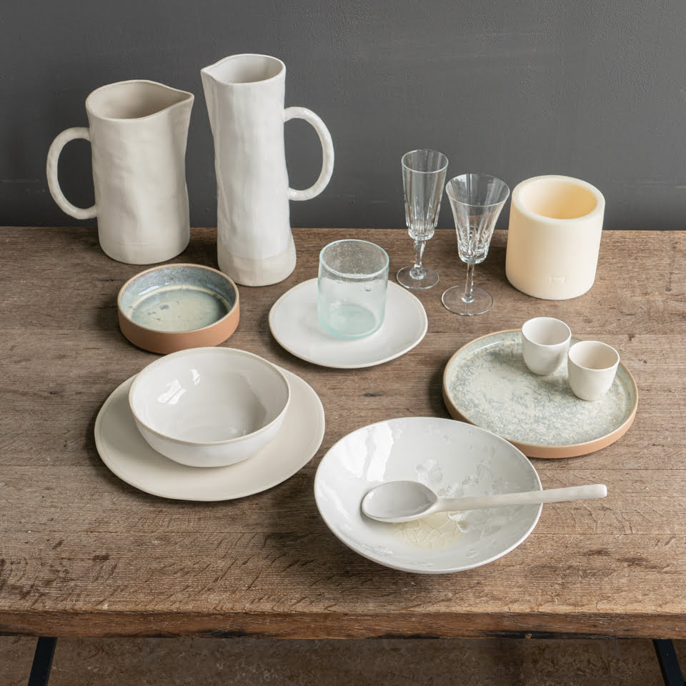 table setting of white plates and dishes on wooden table
