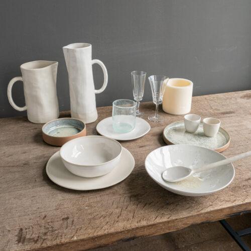 tafelsetting van borden, kannen, glazen en kaarzen op houten tafel
