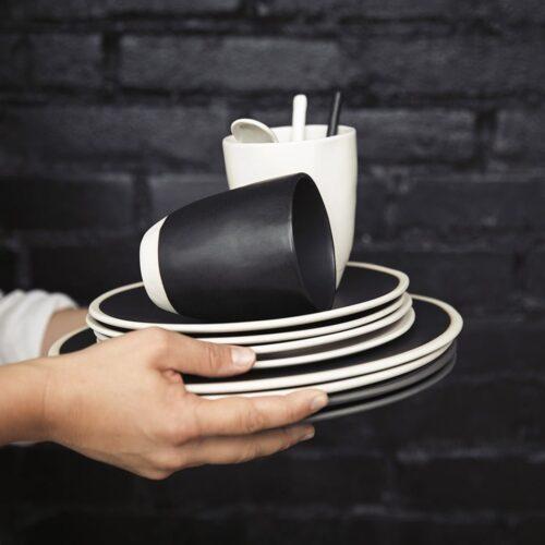 stapel borden en kopjes m zwart en wit die vastgehouden worden voor zwarte muur