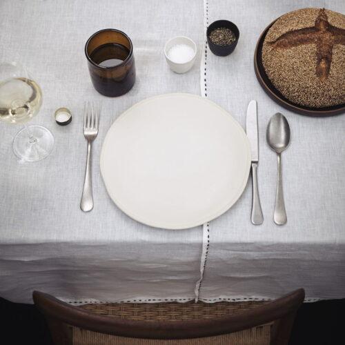 tafelsetting voor 1 persoon van wit bord met bestek, bord met brood, waterglas en kopjes zout en peper