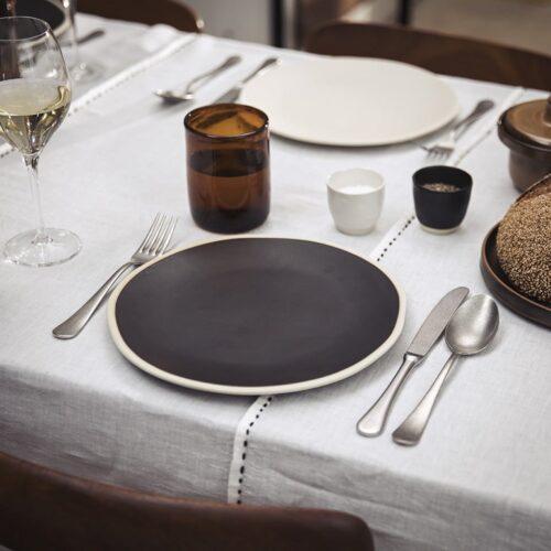 gedekte tafel, linnen tafelkleed met borden en bestek, glazen en peper en zout kommetjes