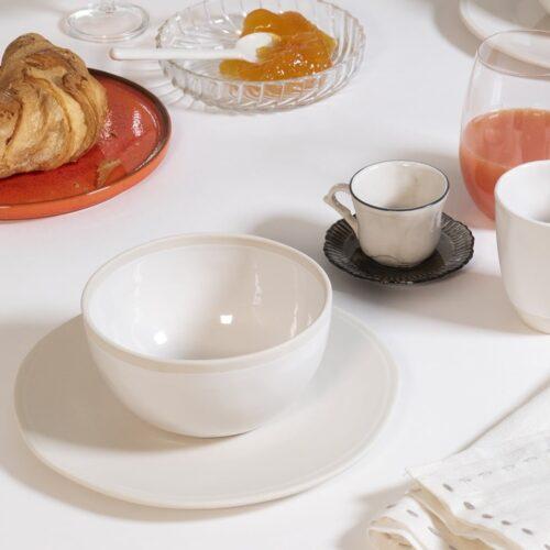 close up van ontbijt setting met witte kom, croissants en kofiekopjes