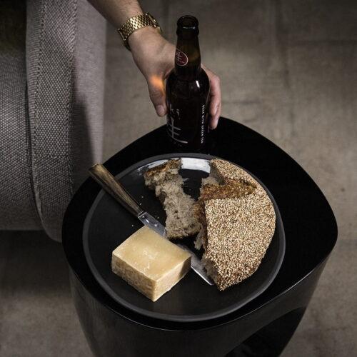 setting van kaas en brood op zwart bord met flesje bier ernaast