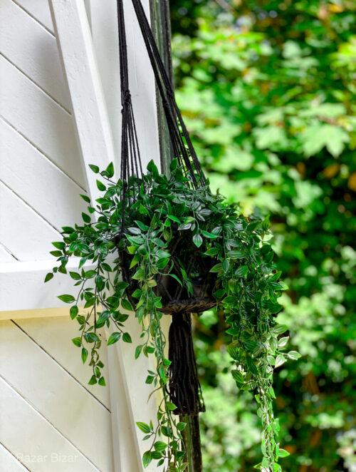 hangplanten in zwarte macrame hanger tegen witte houten buitenmuur