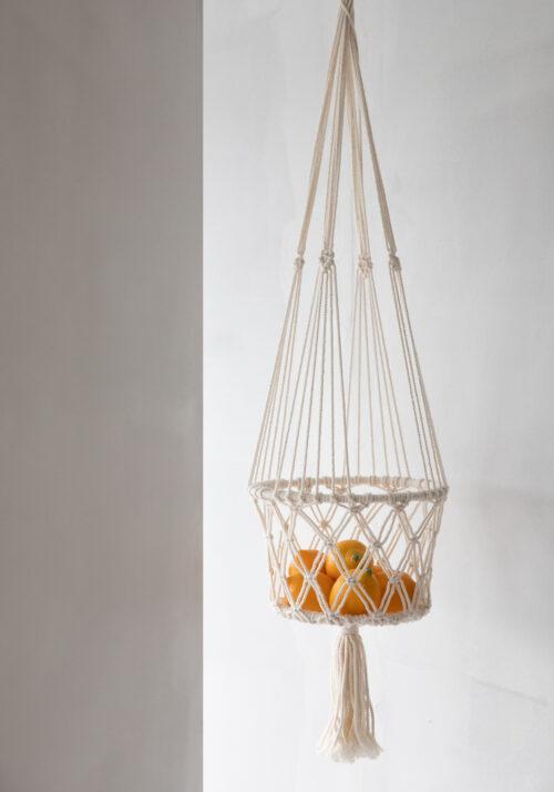 macrame witte plantenhanger gevuld met sinaaappelen hangend voor witte muur