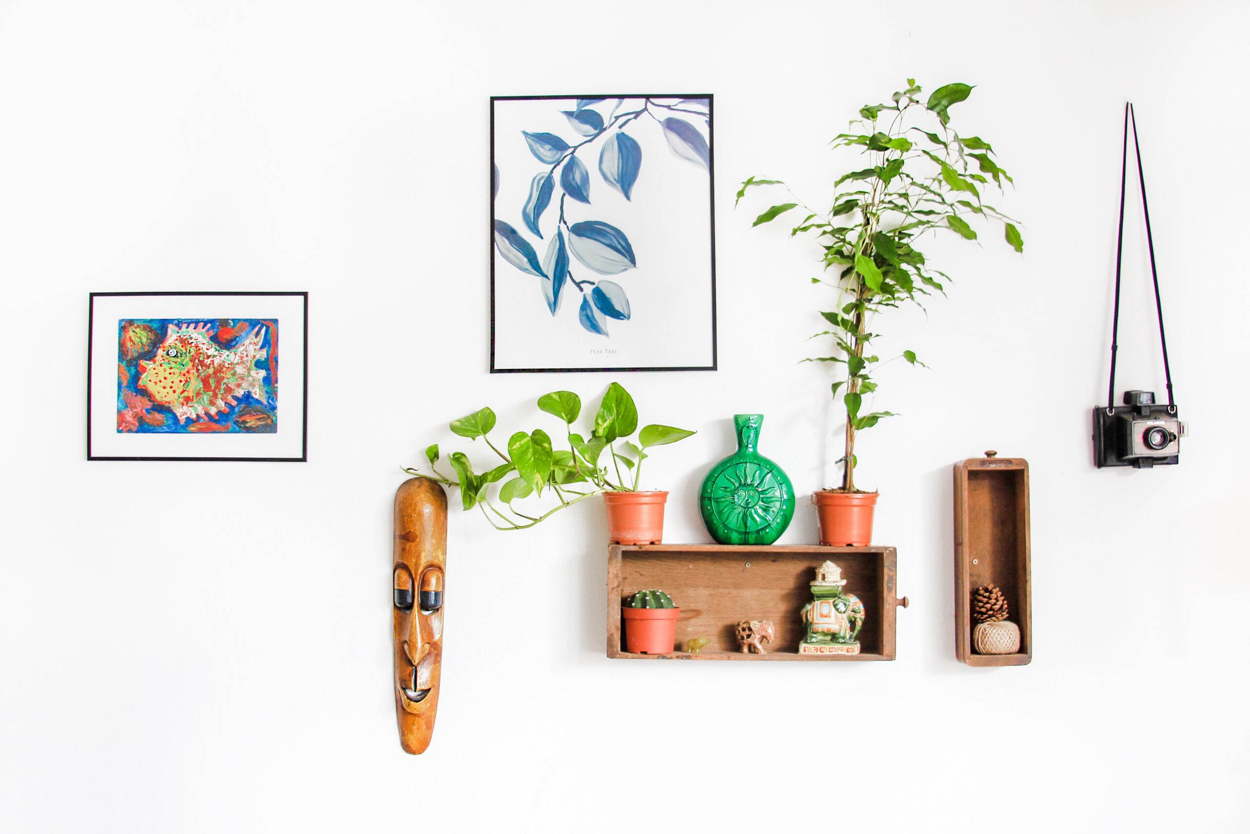 wall with decoration such as painting, wooden mask and vases on shelf