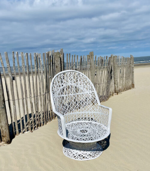 witte gevlochten stoel op het strand voor houten palen
