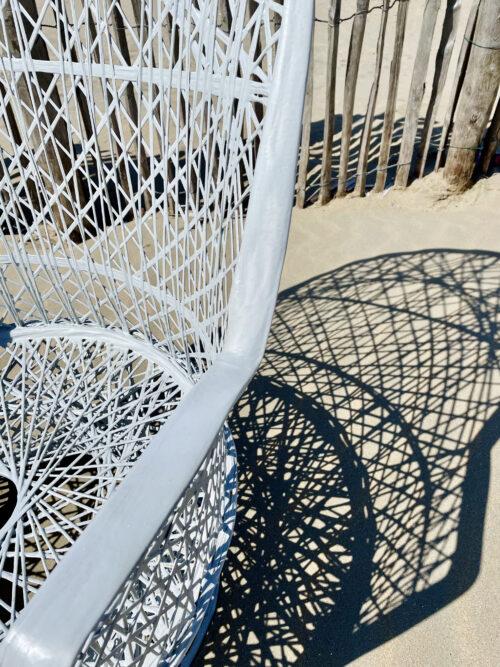 deel van gevlochten witte stoel met schaduw op strand