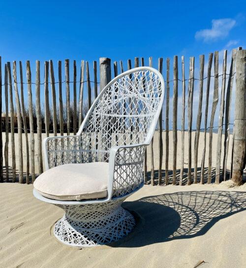 witten gevlochend stoel op het strand voor houten hekwerk