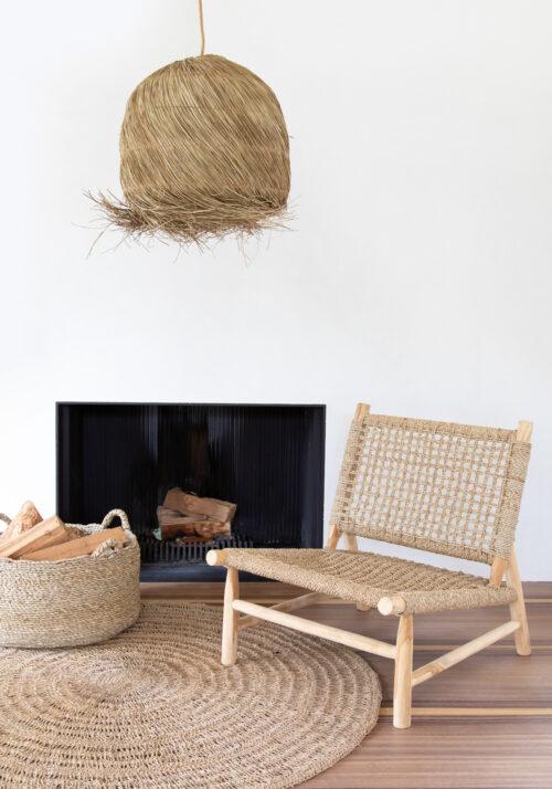 open haard met houten loungestoel, sisal tapijt, sisal lamp en rieten mand met houtblokken
