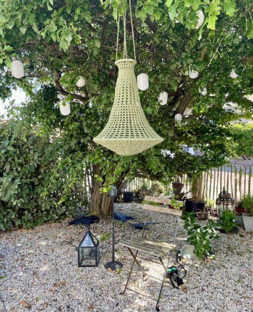 tuin met in boom hangend groene gehaakte kroonluchter