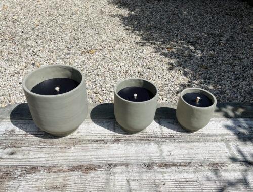 drie zwarte kaarsen op een verweerde houten tafel met rondom grind grond