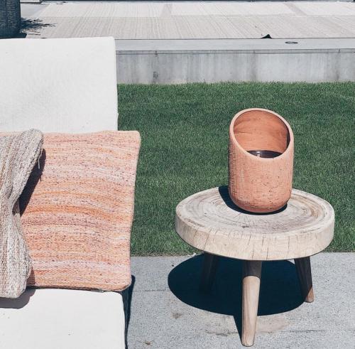 bank met krukje met daarop een keramieken kaars in een tuin