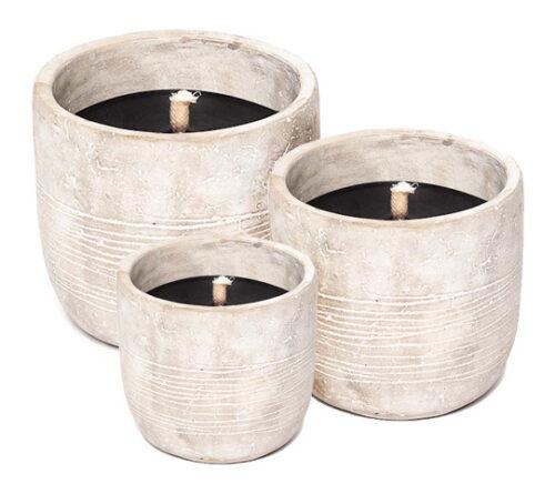 drie kaarsen in aardewerken pot in verschillende maten op witte achtergrond