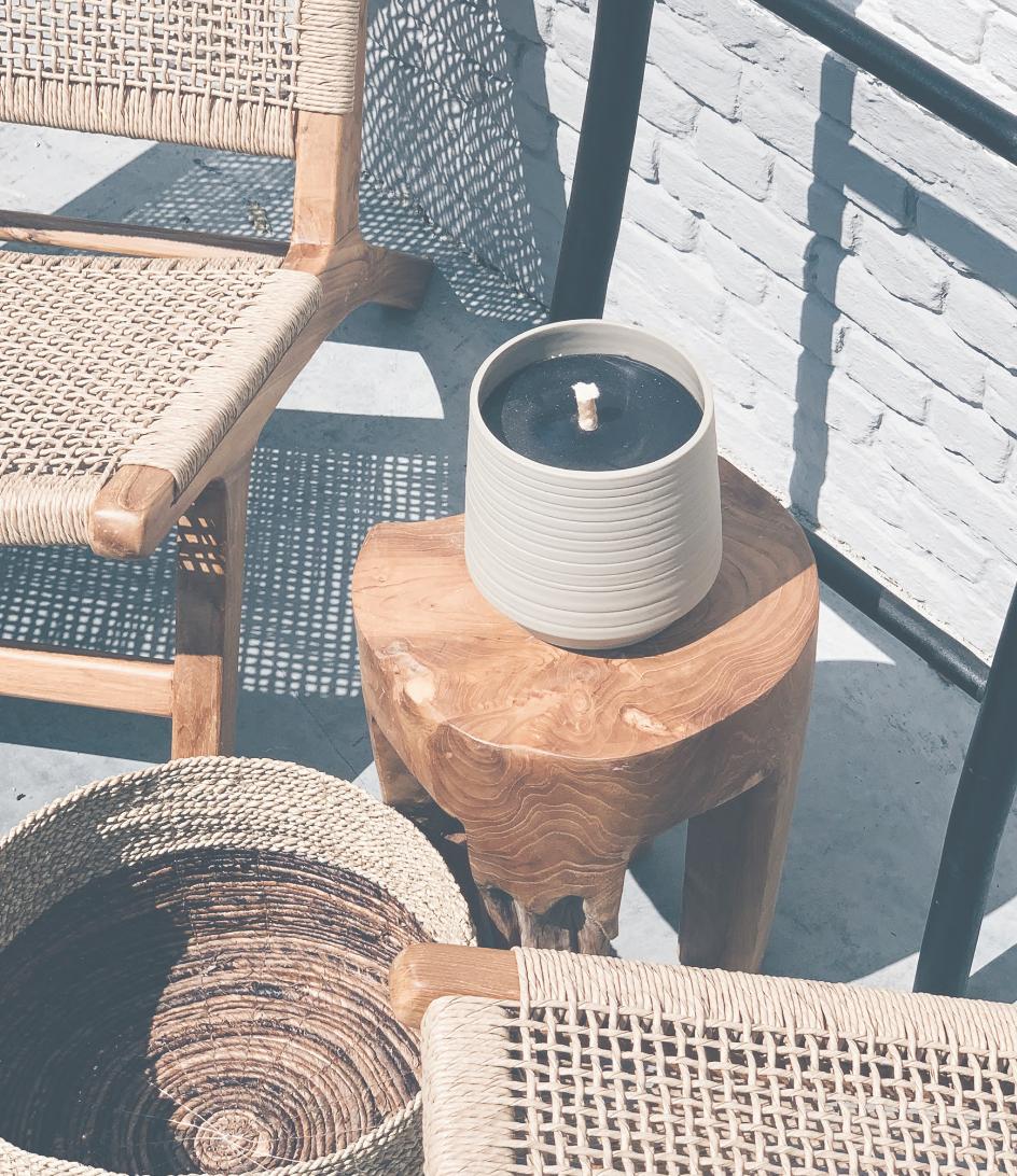betonnen kaars op kruk naast stoel en rieten mand
