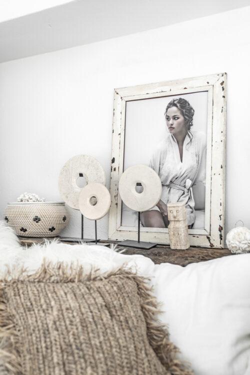setting van wit kleuren met foto in fotolijst en diverse marmeren ronde decoratiestukken op stand en deels een beige kussen in beeld
