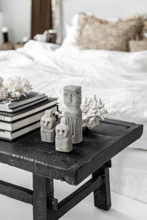 zandstenen beeldjes op zwarte tafel voor een bed geplaatst