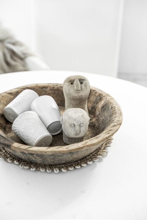 bowl with carved stonemen on a white table
