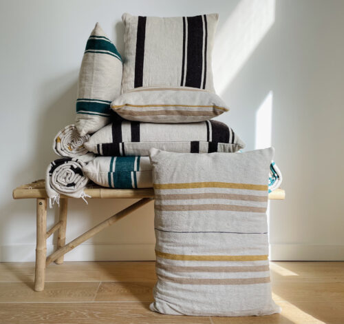 various pillows stacked on top of each other and next to each other on a bamboo bench