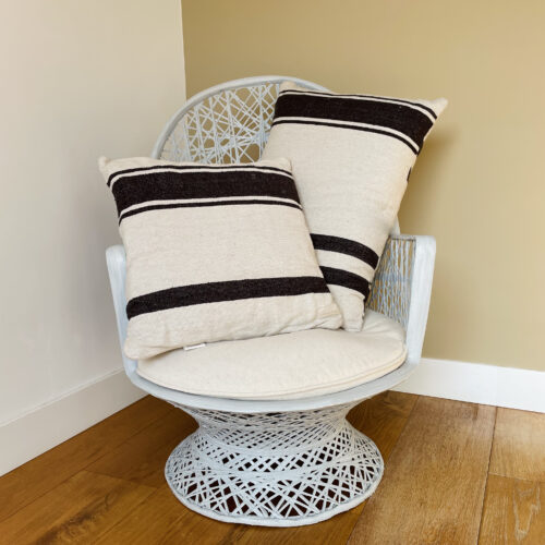 white peacock chair, standing on wooden floor, with two cushions in ecru with brown stripes.